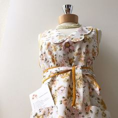 Granny's Apron Classic. Tieback. Charming collar. Botanical floral print. Two button closure at neck. Two pockets in front. Including cranberry chutney recipe in shipping package. Colors: white mustard pink green.❤️ Accessories
