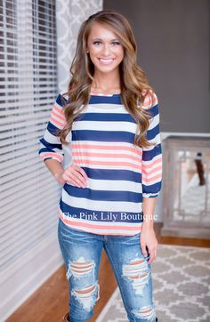 If you loved our Down By The Bay Dress last year, you are going to obsess over this top! Navy, neon orange, and white stripes with a fitted band on the ends of the sleeves and has a small peephole in the back with a button closure!