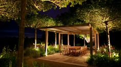 Outdoor dining table surrounded by both a modern pergola and tree groupings.  All well lit by uplighters.