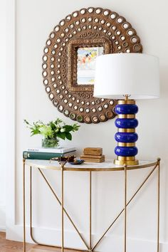 ab23ff8a44f4 Absolutely gorgeous foyer features a demilune brass and marble console  table topped with a blue and