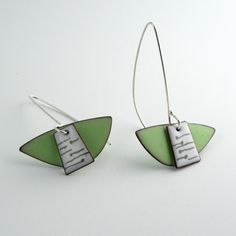 "A pale green matte finish form with a small shiny white piece on top. 1-3/8"" wide, they hang to 2-1/8"".  Enamel on copper with silver ear wires."