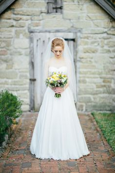 Beautiful bride with yellow and white bouquet, photo by Brooke Images | junebugweddings.com
