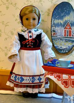 Scandinavian BD: The apron and hat are made from a vintage tablecloth that was at a flea market in Stockholm. The skirt's ruffle and the trim on the pantalettes is a cotton lace. The bodice is navy velvet and is lined with navy satin - by Calyxadollcreations