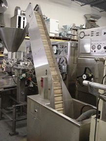 """1-USED STAINLESS STEEL INCLINED FEED ELEVATOR WITH CLEATED BELT AND STAINLESS STEEL FEED HOPPER, 32"""" FROM FLOOR. WITH DYNAMATIC SPEED CONTROL FOR VARIABLE SPEED OPERATION."""