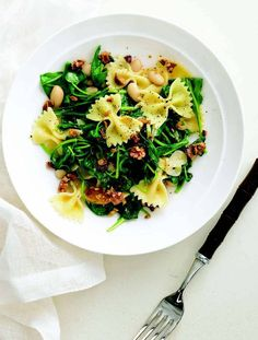 Quickly wilted arugula, canned beans, and toasted walnuts add heft to this vegetarian main course. Try spinach in place of arugula and pine nuts instead of walnuts.