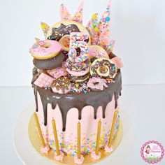 Donut & Sprinkles Birthday Cake - layers of chocolate & funfetti vanilla cake with strawberry swiss meringue buttercream. Decorated with fresh donuts, donut cookies, chocolate donuts, mini chocolate blocks, pink chocolate shards with assorted sprinkles and a dark chocolate ganache drip.
