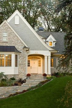 Love the beautiful detail all over this home's exterior.  Stone and shingles, muted colors, arched entry, bay window, dormer, columns, stone walk.  Very welcoming.