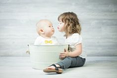 siblings 6 month and 2 year old tub giving a kiss Photo By The Photo Dad