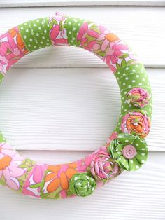 Cover a foam wreath in material and ribbon to match the raggie valence