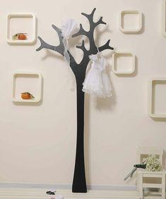 un porte manteau arbre avec une robe de petite fille