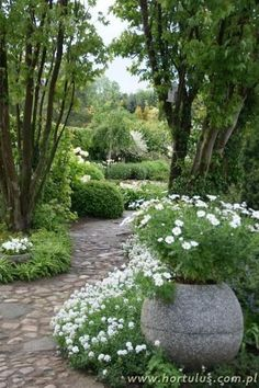 The Green & White Gardens: Cobblestone path and the container in soft grays quietly relate, reinforcing the tranquility of the two garden spaces.