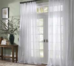 These drapes are beautiful against the sage green walls in this entry way. Lets in light and character with the double open french doors and square windows