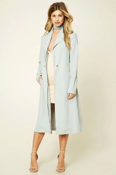 A longline faux suede coat by Bellfield™ featuring wide layered lapels, a single snap buttoned closure, a self-tying sash belt, dual slanted front slip pockets, a vented back, and long sleeves.
