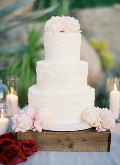 Classic white cake with the most intricate Spanish lace patterns and the palest of pink of peonies