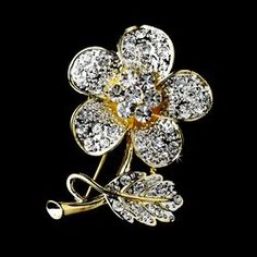 Bloom with this beautiful floral brooch featuring crystals and rhinestones all set in a beautiful gold-plated backdrop. Elegant petals and leaves decorated with glittering stones. Wear with any outfit for a fashionable accent.    Size: (Height) 2'', (Width) 1.5''    Also available in Silver Clear.