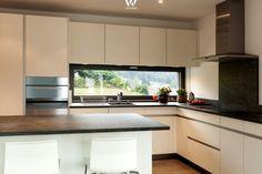 Dank dem breiten Fenster kann beim Kochen der Blick in die Natur genossen werden - Wohnidee by WOONIO