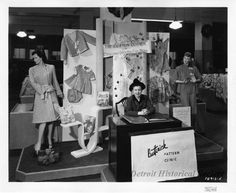 """Miss Isabelle Warren sits at a desk, with her hands folded and placed upon Butterick pattern books. Signage affixed to the rear display reads, """"The Cotton Corner, For Christmas Gifts You Can Make,"""" and includes options for gifts including children's wear, aprons, and sleepwear. Two female mannequins flank the left and right sides of the rear display and each are modeling available options. Signage to the right of Miss Warren reads, """"Its Christmas Time at Hudson's,"""