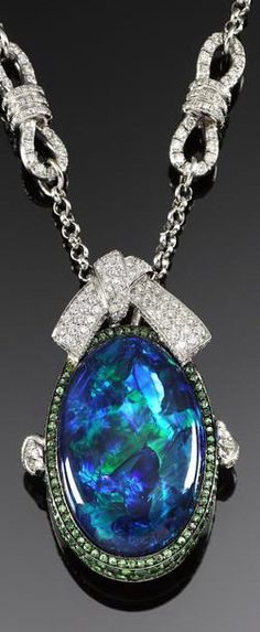 Stunning 22.63-carat Australian Black Opal Pendant.  Accented with 2.50 carats of tsavorite garnets and 1.50 carats of diamonds (all set in 18k white gold), that opal is amazing. Mauboussin has always been known for a particular expertise in colored stones, and this piece really allows you see the artistry in gem-setting and jewelry design, as the garnets perfectly complement and draw out the green within the opal.