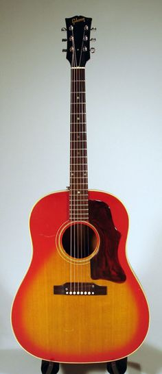 1967 Gibson J45 red sunburst.  Burnt orange top vigilantly checked over the course of a 40-year journey, bursting with responsiveness. Sweet slender neck beckons. Tremulous treble and lilting sweetness characterize the prowess of this acoustic, blue-collar beast. The Hummingbird has landed!  3795 dollars.