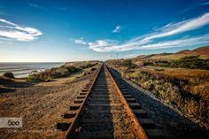 Rails to nowhere by grooveman222  beach beautiful blue clouds ocean rail road rocks sand sea seascape sky sun tracks travel trees wate