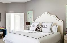 """The master bedroom is one of Paloma's favorite spaces. """"It is kind of a departure from the rest of the home,"""" she says. """"It's much more feminine and glamorous."""" Adding to the drama area sumptuous upholstered headboard, monogrammed linens, and silk wall panels on both sides of the bed."""