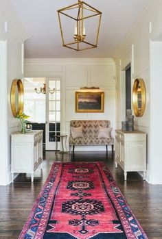 Accessories give a space its personality.  This entryway shines with its rug and gold mirrors.