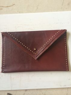 Dark wine leather clutch with gold stud closure and double stitch detail.