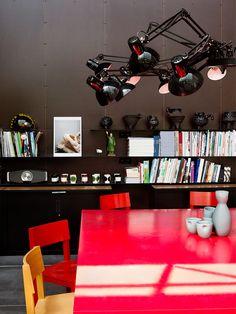 """Hans Lensvelt huis is een opmerkelijke gerenoveerde boerderij met de steun van architect Eline Strijkers. Een woon- annex conferentiehuis. Heldere rode fauteuils Boutique Diary van Marcel Wanders (Moooi) verlichten de selectie van de bruine tinten. Een interieur met strakke design en een vleugje humor. """"Dear Ingo"""" hanglamp van Ron Gilad (Moooi) ontvouwt zich boven de AVL Shaker tafel. AVL Shaker Chairs van Joep van Lieshout en fauteuils """"Smoke Chair"""" van Maarten Baas (Moooi)."""