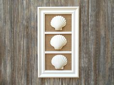 The perfect gift for the stylish woman in your life! This beach wall art measures 8 1/4 x 14 1/2 inches (measuring outside dimensions) and would be a lovely addition to your home whether hung on the wall or lean on a mantel. Each lovely sea shell is a different size and shape as you would find in the natural and is not covered by glass adding depth and dimension. The frame is a matte white and I added natural color burlap for interest and texture. I can affix the shells to display e...