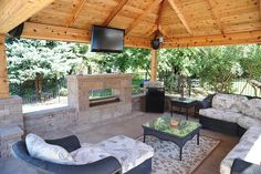 Cedar isnt my jam but, what a great space! Outdoor living room with fireplace, TV with surround sound, paver brick floor, and seating area, all underneath a beautiful cedar outdoor living structure, done by All Seasons Pools and Spas in Orland Park, IL