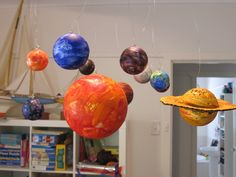 Materials:  10 styrofoam balls (1 very big for the Sun, 2 large for Jupiter and Saturn, 4 medium for Uranus, Neptune, Venus and Earth, 3 small for Pluto, Mars and Mercury),  a small hoop,  little picture hooks,  wire/fishing line,  a small piece of cardboard to make Saturn's ring and paint.