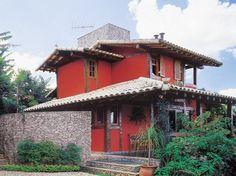 Vermelho na parede, branco na cobertura: a casa de campo, numa cidade a 40 km...