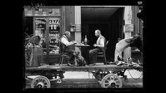 Scène de rue : un repas sur un camion, devant un commerce de café et de liqueurs. Paris, fin mai 1917.