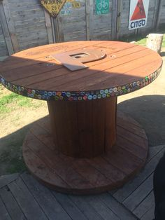 Repurposed spool. Sand, stain, decorate with bottle caps. Redneck table.
