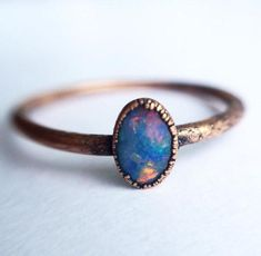 A small oval Australian opal has been electroformed to a hand hammered 16 gauge copper ring.Every stone is as unique as the person it will adorn. Please allow f