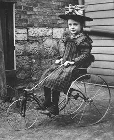 Adelia Matter on a tricycle, c. 1900. Adelia has a child's replica of the large, flower hats of the day. The trike has all metal wheels yet the padded seat compensates. Photograph by Walter Matter of Chicago.