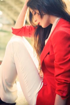 adore the vibrant red combined with a slim cut creme trouser in this shot by photograph by Nadia Moro
