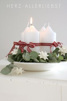 Love this—Advent candle arrangement—red & white striped ribbon, white oragami stars, & eucalyptus greenery❣