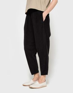 From Black Crane, a lightweight pant in Black. Featuring an elasticized waistband, pleats at front, two slit pockets at side seams, dropped crotch, slightly cropped length, tapered leg and a relaxed fit. • Pant in Black • Elasticized waistband • Plea