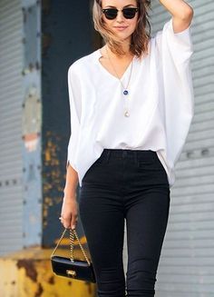 White loose blouse and mini lockets with high waist black skinnies.