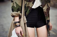 oversized camouflage shirt and high-waisted black shorts