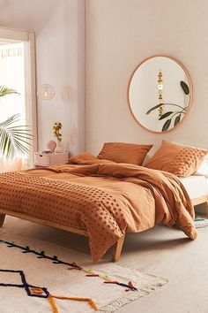 Tufted Dot Duvet Cover | Urban Outfitters. Love this cozy bedroom with bohemian and modern decor. Room is tied together by the rug with fringe edge and the round mirror.