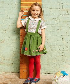 Little Bird Cord Skirt and Braces. With detachable braces, this super sweet and stylish cord skirt features colourful tulip applique and ditsy printed fabric detailing and will look adorable styled with a pair of cosy tights and a pretty sweater.