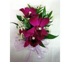 Dark purple dendrobium orchids accented with white limonium, silver studs and iridescent purple bow.