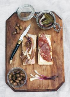 wood cutting board with meats and olives