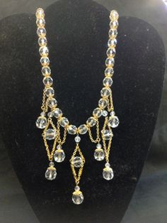 STUNNING ART DECO ERA HEAVY FACETED CRYSTAL NECKLACE WITH MULTIPLE DROPS. THIS FABULOUS VINTAGE PIECE HAS LARGE CRYSTALS WITH GOLD TONE CAPS, STRUNG ON A METAL CHAIN. IT CERTAINLY COMMANDS YOUR ATTENTION. MEASURES 16 INCHES IN LENGTH.