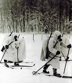 Finnish infantry equipped with gas masks and white camouflage advancing on cross-country skis during the Battle of Suomussalmi, 1939-1940. Winter War