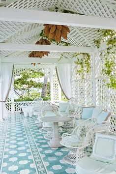 Cabana with vintage furniture in Outdoor & Alfresco Dining Room Ideas. White metal garden furniture decorated with pale blue cushions, Wicker work and Patterned tiles.