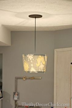 A tutorial on how to transform a lamp shade. All you need is some fabric, scissors and a hot glue gun!