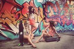 The models relaxing with suitcase and skateboard in hand at Mermaid Beach by a graffiti wall.